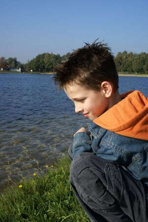 Boy sitting in grass enjoying the lake. photo