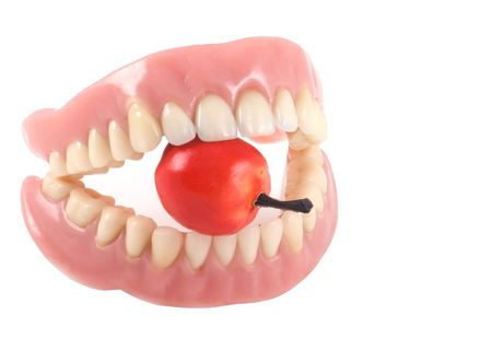 molars: Dentures with little fake apple, isolated on a white background.
