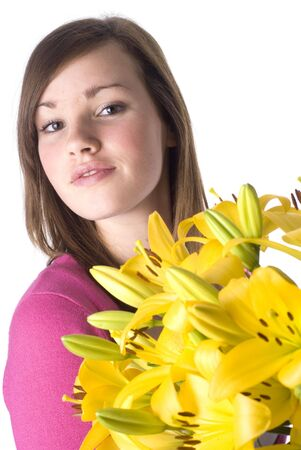 Beautiful girl with a bunch of yellow lillies; isolated on white. photo