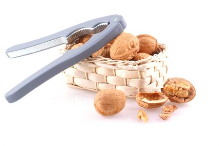 Basket full of walnuts with nutcracker, isolated on white. Stock Photo - 4001306