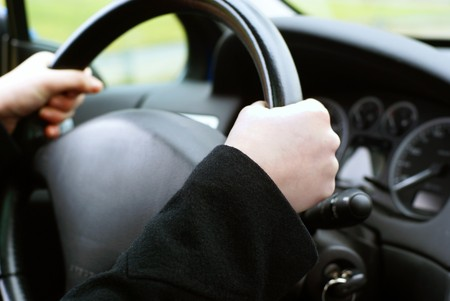 Chauffeur: Two hands on a wheel, in the background the car interior. Stock Photo