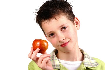 Boy holding up an apple on white.       photo