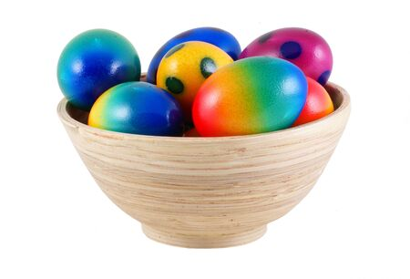 Easter eggs in wooden bowl, isolated on white. photo