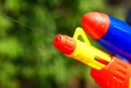 watergun: Close up of a water pistol in front of green bushes.