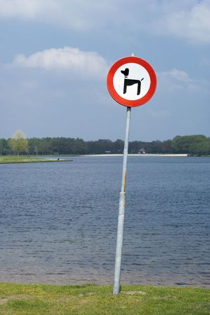 No dogs allowed traffic sign in front of a lake. photo
