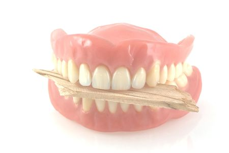 pauper: No money to eat, dentures biting on a piece of wood, isolated on white.