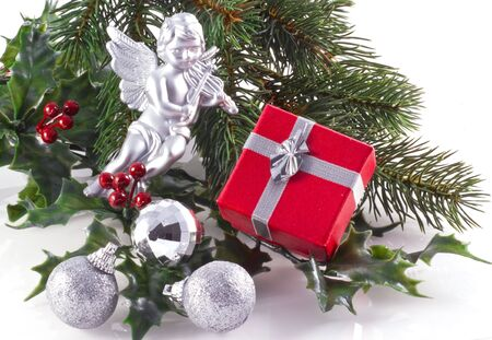 Red giftbox, silver christmas ornaments and part of a christmas tree, on a white background. Stock Photo - 5756320