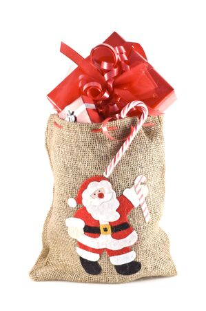 Bag with santa print, full of christmas presents isolated on white. photo