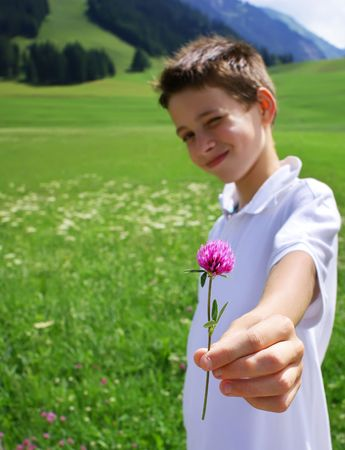 Boy in mountainous environment giving wild flower. photo