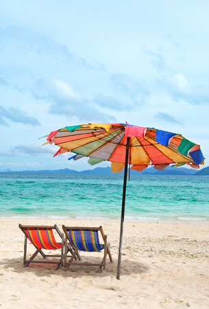 Beach chairs and colorful umbrella on the beach in sunny day, Phuket Thailand photo