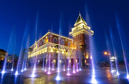 coloured jets water of fountain and the Main Guard building by night in the Venezia Huahin Thailand Editorial