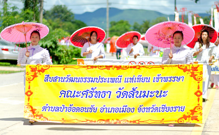 Chiang Rai - July 24   Wat Rong Khun taken on July 24, 2013 Parades of thai Buddhist wearing White Candle Art Parade Festival on raining season at White Temple,Thailand  Editorial