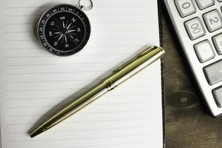 succession planning: Compass pen and calculator there are other items in your desktop Stock Photo