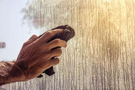 young man brushing the window.