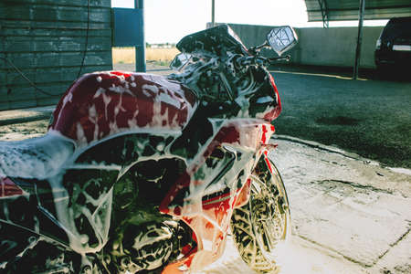 cleaning red sportbike in the car wash Archivio Fotografico