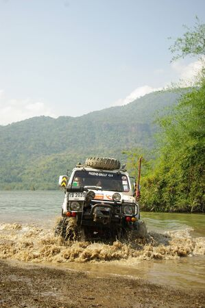 fourwheeldrive: KANCHANABURI THAILAND - MAY 15 : Unidentified man drive Suzuki Caribien to testing ability of modified equipment and suspention for use on the barrens route on May 15,2006 at Srinakarin reservoir, Ban Krai Kriang, Kanchanaburi, Thailand.