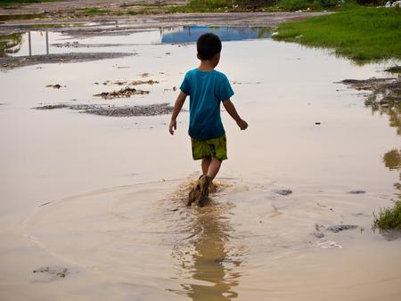 muddy: A Boy walkl in dirty muddy water Stock Photo