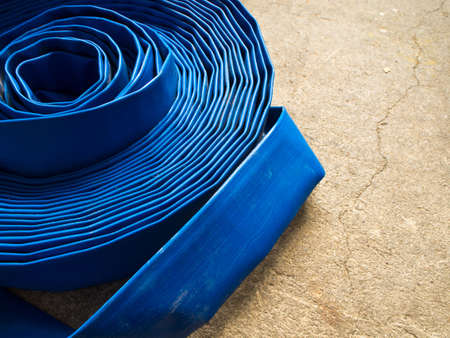 crack pipe: Blue canvas hose rolled on the concrete floor
