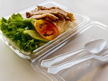 Geroosterd varkensvlees en rijst in een plastic doos