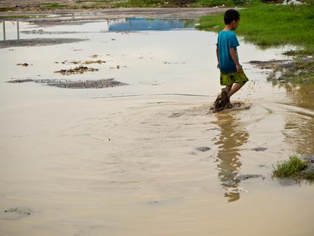 muddy: A Boy stroll in dirty muddy water Stock Photo