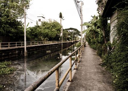 aguas residuales: Manera de la caminata concreto a lo largo del canal de aguas negras