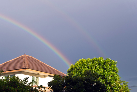 rooftile: Big rainbow over the roof Stock Photo