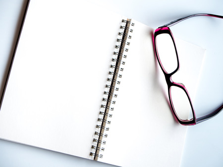 blank page: Blank page of a spiral notebook and eyeglasses