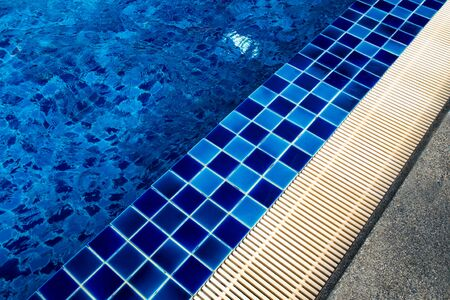Blue Ceramic tile flooring and drainage gutters beside the pool
