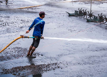 CHACHOENGSAO THAILAND - JULY 13 : Unidentified men control high pressure water jet nozzle to clean the mud at the bottom of the pond on July 13, 2016 to prepare the pond clean, for next time shrimp farming, Chachoengsao, Thailand.