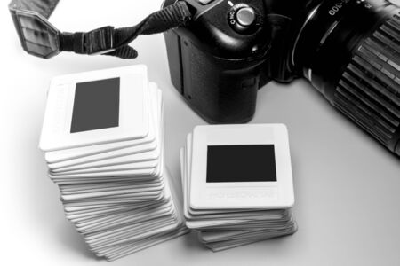 Stack of old reversal slide film in plastic frame and part of camera Stock Photo - 87390993
