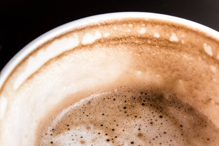 decreased: Stain of Hot milk coffee and soft froth inside the white ceramic cup, Half a cup of coffee Stock Photo