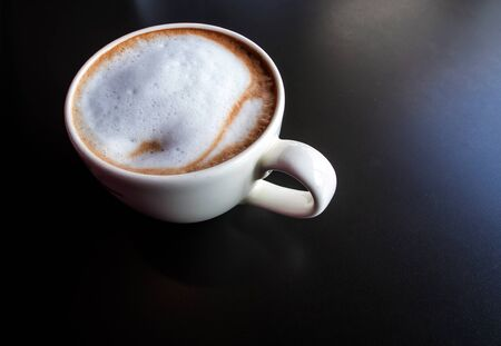 Hot milk coffee and soft froth in white ceramic cup