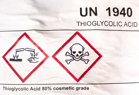 Warning symbol on label sticker of corrosive material at the acid container