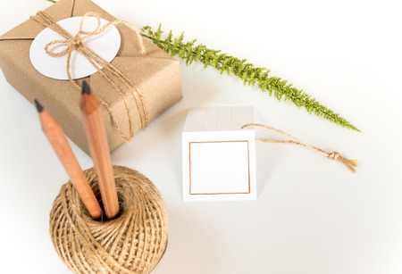 Brown gift box wrapped in kraft paper and rustic hemp cord spool as natural rustic style with paper and pencil for write your note