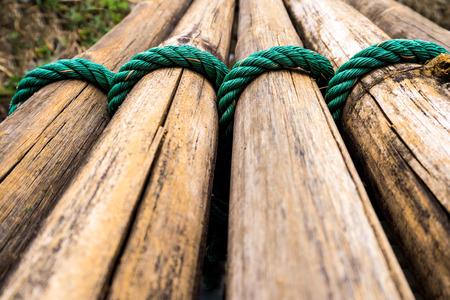 Dried bamboo tie with green nylon rope as a small bridge Archivio Fotografico