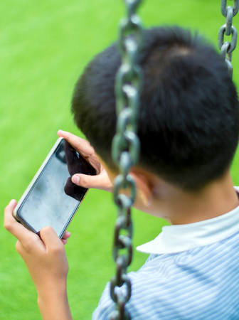 Serious boy playing on smartphone, Children playing game on smartphone Stock Photo