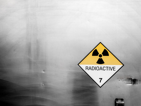 Radiation warning sign on the Hazardous materials transport label Class 7 at the aluminum container of transport truck Stock Photo
