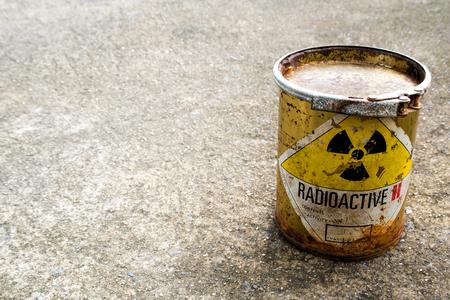 Panneau d'avertissement de rayonnement sur l'emballage rouillé du conteneur de matières radioactives sur le sol en béton brut