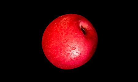 Close-up of Water droplet on glossy surface of freshness red apple on black background