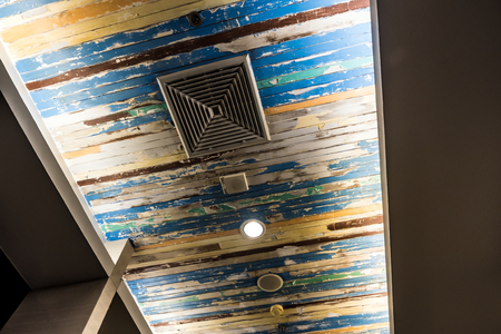 Air conditioner mask, lighting and modern equipment On the ceiling that decorated with old wooden panels and peeling paint