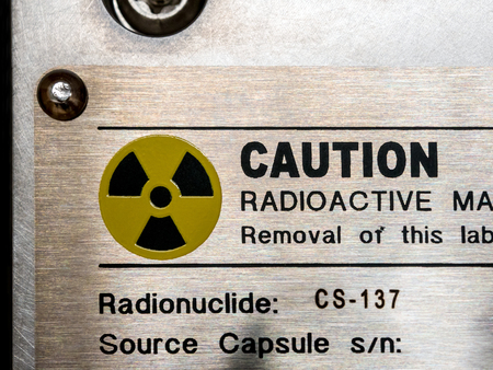 Radiation warning sign on the nameplate and the machanical container of factory process instrument, Ionizing radiation hazard symbol as background