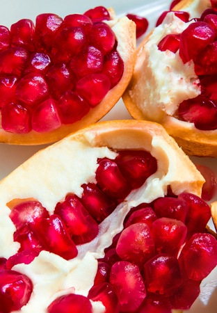Top view closeup image of red pomegranate seeds on pomegranate seeds pile present a detail of pomegranate seeds texture, fruit background, red background Stock Photo