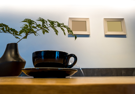 Coffee in black cup with ornament fern on wooden table
