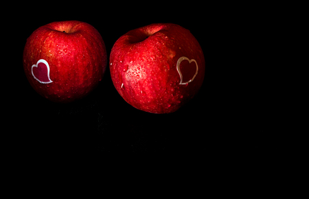 Heart shape sticker and water droplet on glossy surface of freshness red apple on black background