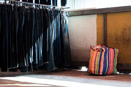 Multi color on Plastic sack and the row of denim pants hanging on trempels. Jeans in clothing store