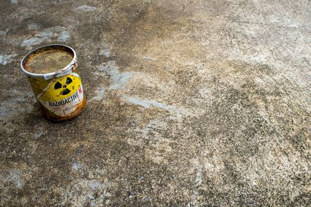 Radiation warning sign on rusty package of radioactive material container on the rough concrete floor Stockfoto
