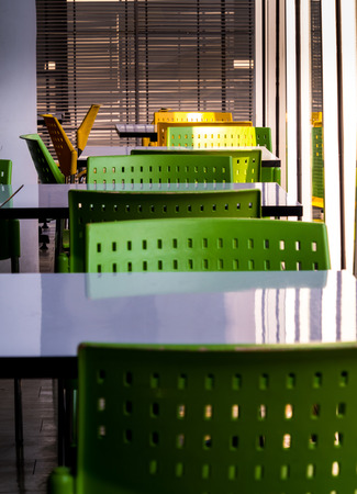 Empty white tables and green color plastic chairs that nobody sit in the cafeteria