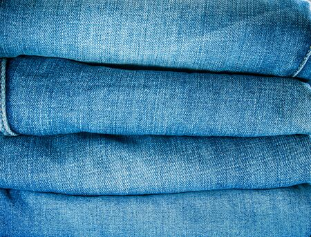 Pile of different blue jeans, fabric texture