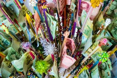 Thai banknotes clamped at the end of the wood Decorated with colored paper and lace together to prepare to give to the temple