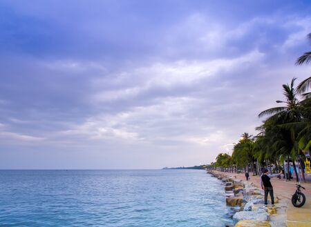 The sea is calm and the sky's overcast with rain clouds in the morning of the coastal area